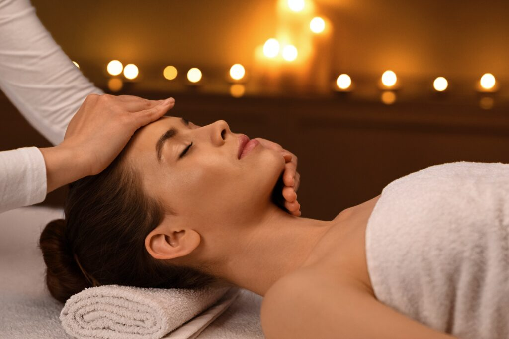 Sleeping woman getting healing face massage at spa