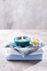 Spa resort therapy composition. Burning candles, towel and flower on a stone background, copy space